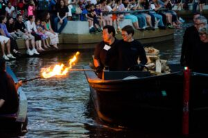 Captain Jane lines up her guest lighter's torch for the WaterFire lighting ceremony. Photograph by Tom Lincoln.