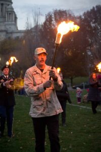 WaterFire volunteer Doug Fox carries a torch during the Veterans Torch Salute. Photo by Jessica Ho.