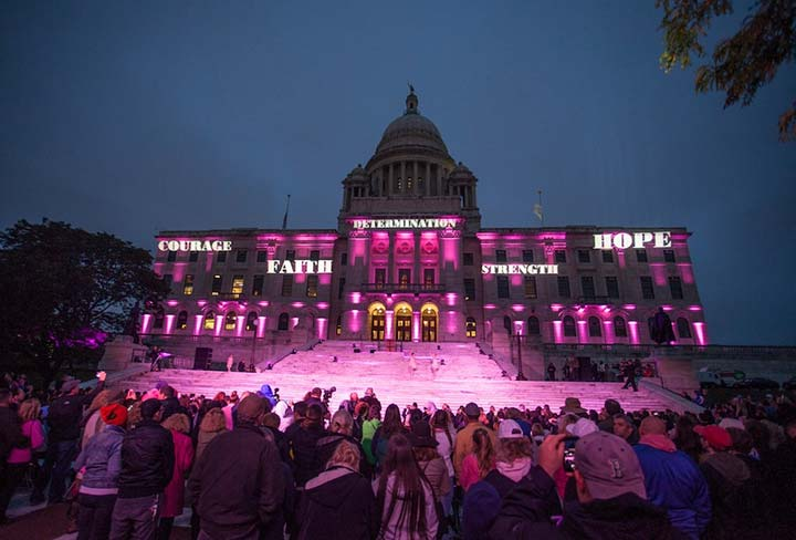 Lighted State House at dusk to honor breast cancer survivors. Photograph by Erin Cuddigan.