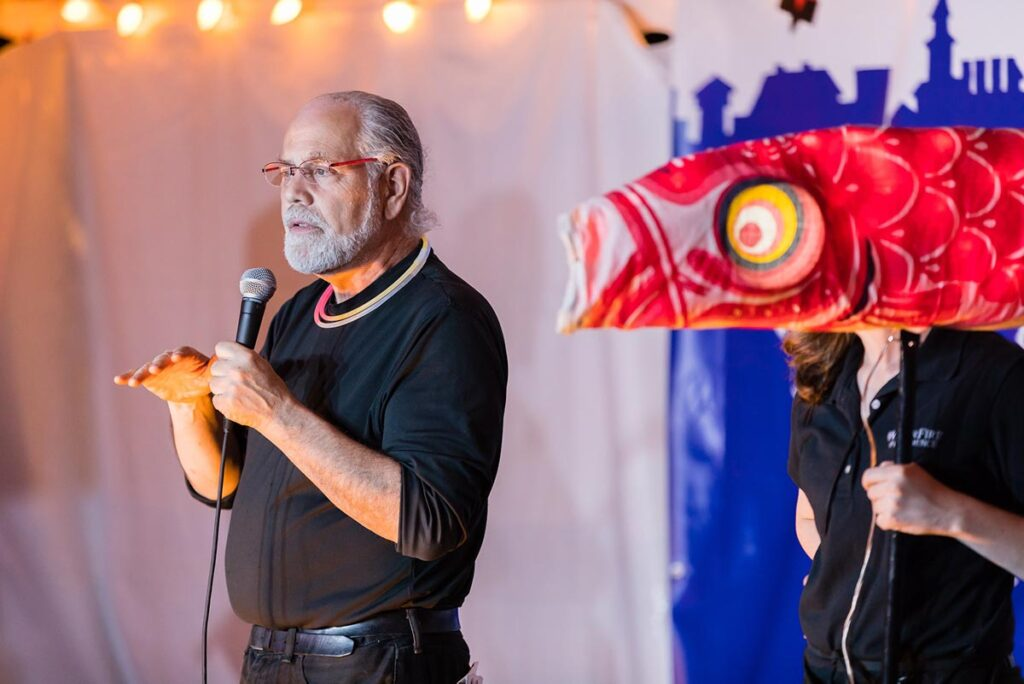 Barnaby Evans, WaterFire creator and Executive Artistic Director/coCEO of WaterFire Providence, speaks at the Olneyville Expo in 2019. Barnaby is seen on stage along with one of our LED illuminated Japanese Koi fish. Photograph  by Matthew Huang