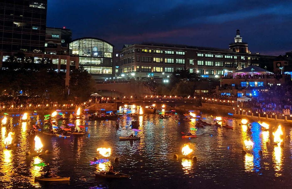 A view of the Basin in Waterplace Park shot during the 2019 Clear Currents Community Paddling Event. Kayaks with Illuminated Koi fish attached circle the ring of braziers in the Basin. Photograph by Tim Blankenship