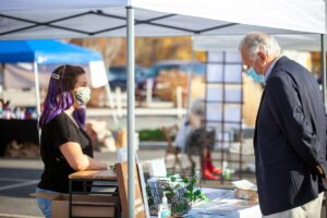A customer peruses prints at the Fernweh Prints Co booth during a 2020 ArtMart Market. Photograph by Erin Cuddigan.