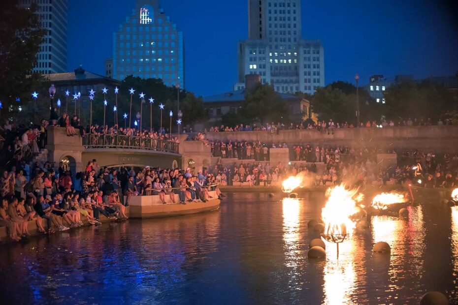 Fires illuminate the faces of the crowd in Waterplace Park during a WaterFire lighting in 2018. Photograph by Jen Bonin.